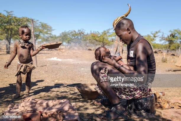 Young Himba boy with a traditional hairstyle holding a baby on his lap while a child passing by is looking at them.