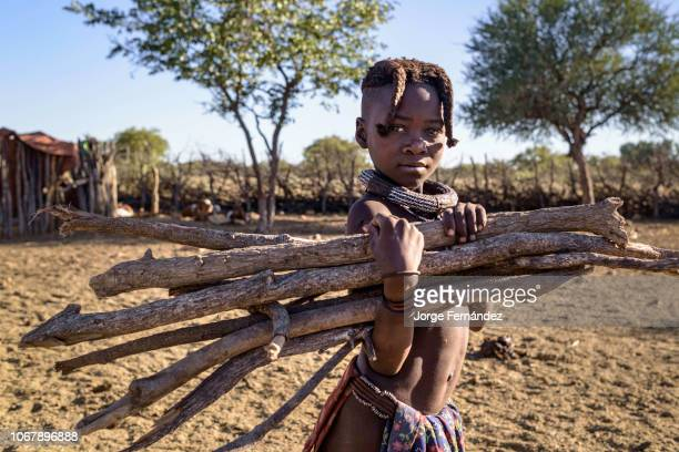 Young Himba girl collecting firewood in a village.