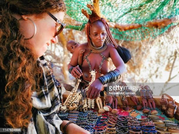 jeune femme himba vendant des bracelets à un touriste au décrochage de marché de village - femme himba photos et images de collection