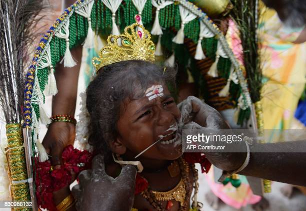 TOPSHOT A young Hindu devotee reacts in pain as his cheeks are pierced with a metal rod during a ritual on the occasion of 'Aadi' festival in Chennai...