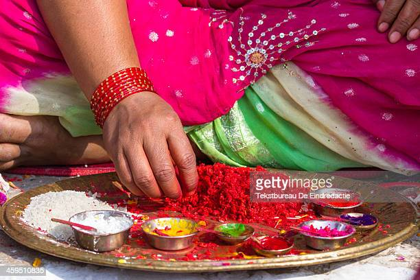 CONTENT] A young hindu woman wearing a colorful sari preparing a tika at the temple during Bhai Tika the fifth day of the hindu festival of Tihar...