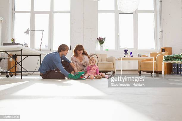 a young hip family playing together on living room floor - junge familie stock-fotos und bilder