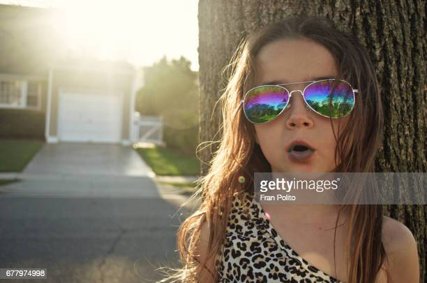 A young hip girl wearing sunglasses.