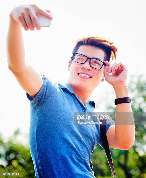 Young hip Vietnamese male tourist shoots selfie adjusting glasses