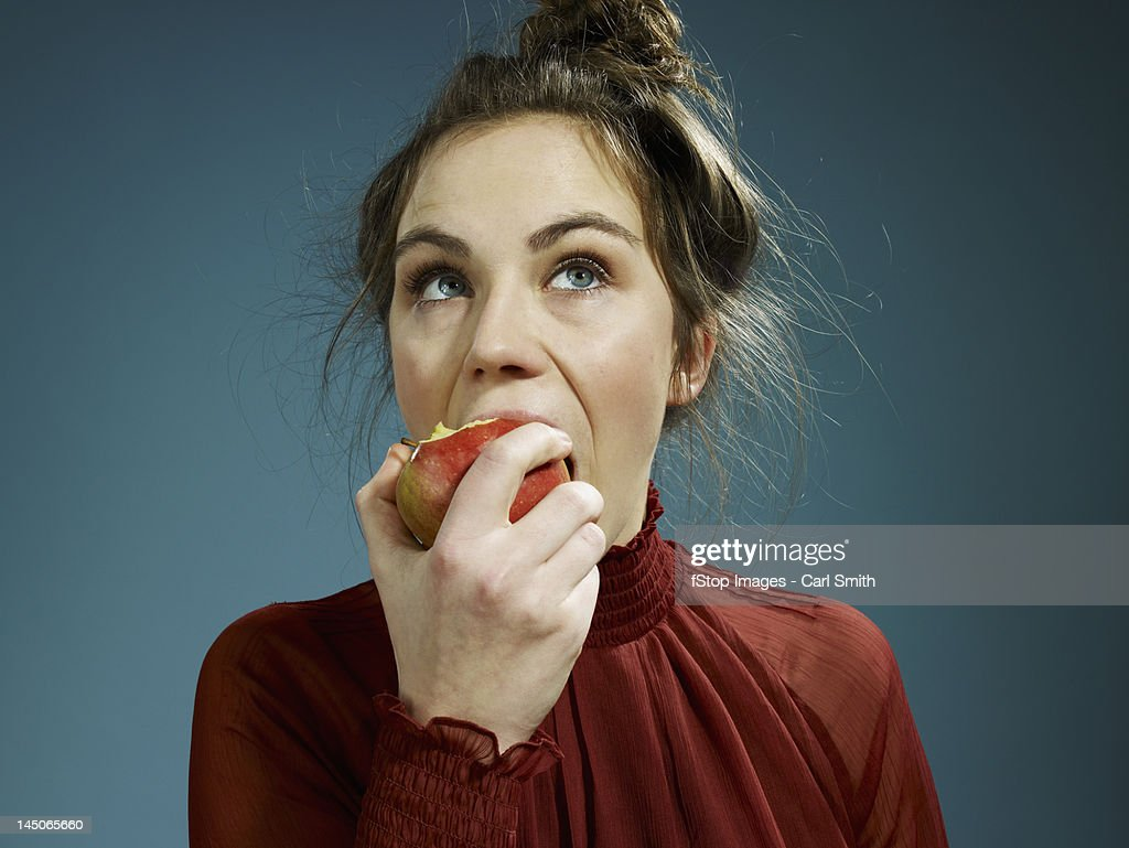 A young hip woman eating an apple : Stock Photo