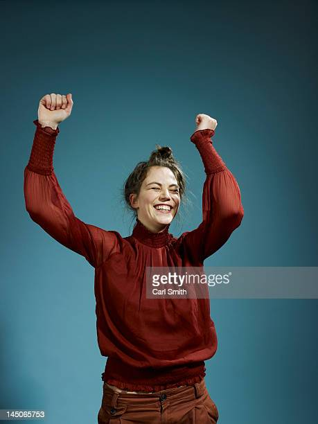 a young hip woman with her arms raised in celebration - vreugde stockfoto's en -beelden