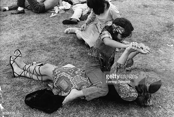 A young hippie child plays with his mother at the Hyde Park Pop Festival during an interval
