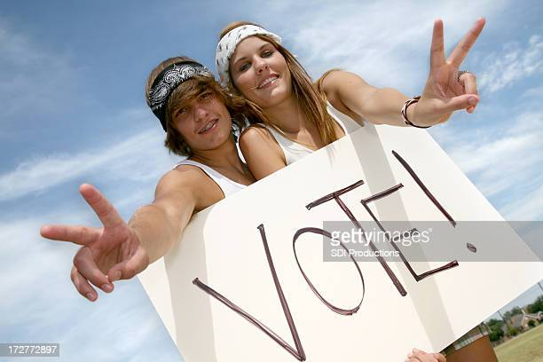 Young Hippie Couple Holding Vote Sign Making Peace Hand Gesture