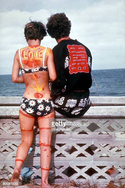 Young hippie couple she bikini clad and painted w psychedelic designs looking out at the sea during a lovein fest