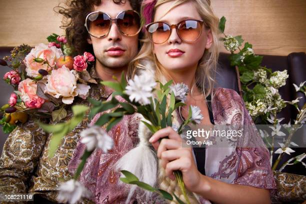 Young Hippie Man and Woman Holding Flowers