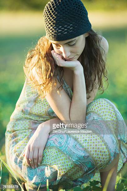 Young hippie woman crouching in grass, looking down