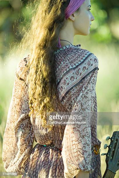 Young hippie woman holding guitar, rear view
