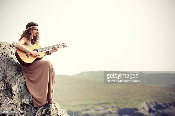 young hippie woman playing guitar on a cliff, a coruna - carmen bella foto e immagini stock