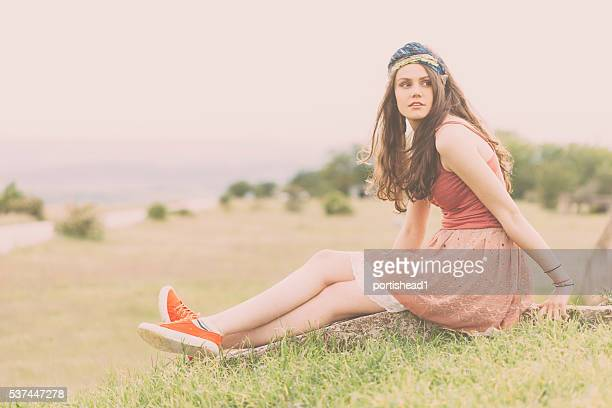 Young hippie woman sitting in the field