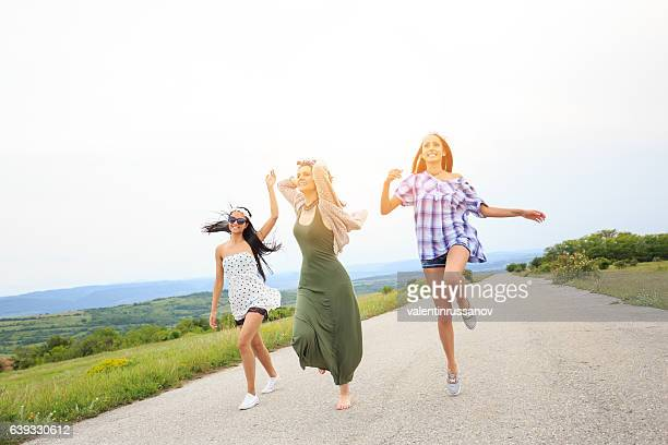 Young hippie women dancing and having fun on the road