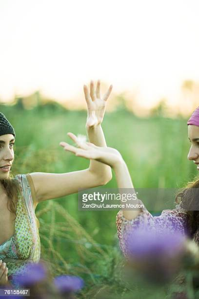 Young hippie women, hands up catching dandelion seed heads