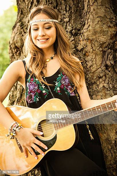 Young hippy woman playing guitar
