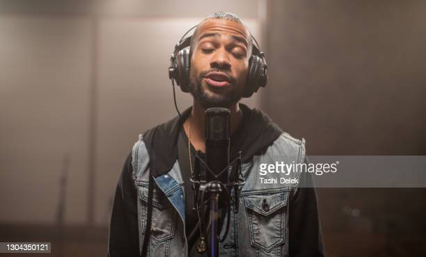 young hipster african-american rapper recording songs in music recording studio - pop music stock pictures, royalty-free photos & images