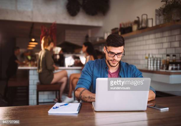 young hipster businessman working on laptop at urban coffee shop - intelligenza foto e immagini stock