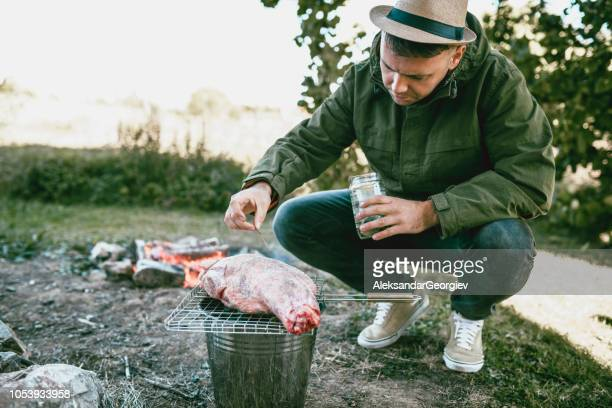 Young Hipster Chef With Straw Hat Seasoning The Meat For Perfect Taste