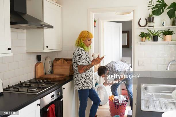 young hipster couple doing their laundry - couples showering stock pictures, royalty-free photos & images