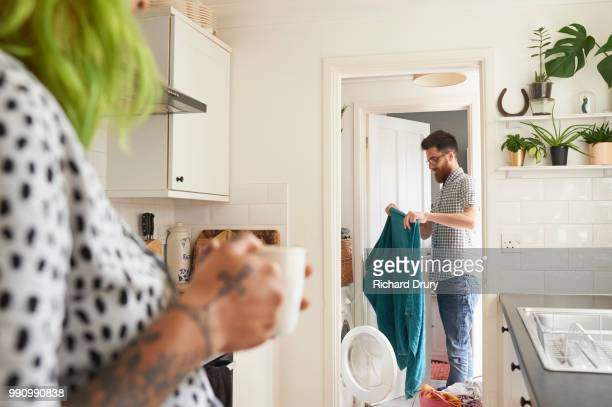 young hipster couple doing their laundry - hausarbeit stock-fotos und bilder