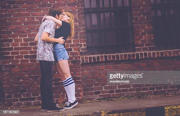 Junge Hipster-Paar Küssen gegen grunge-Gebäude
