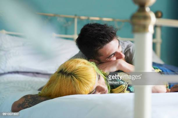 Young hipster couple lying on their bed together