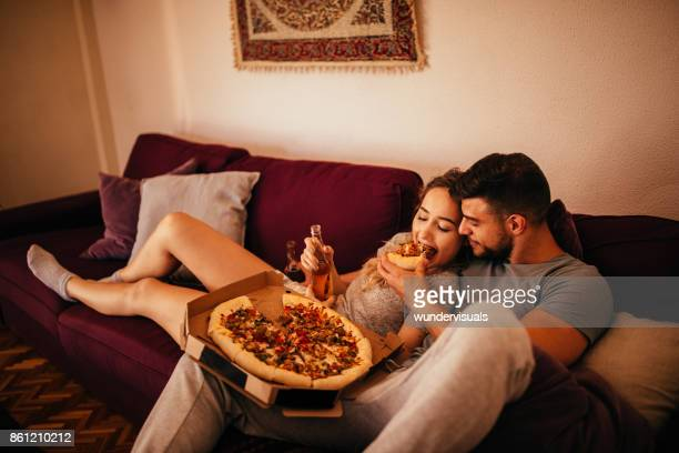young hipster couple relaxing on the sofa eating pizza - weekend activities stock pictures, royalty-free photos & images
