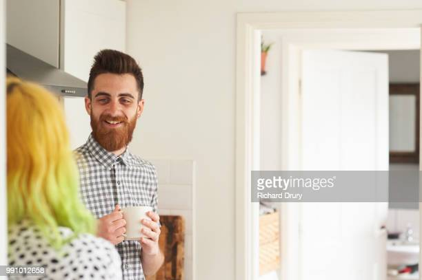 Young hipster couple talking in their kitchen