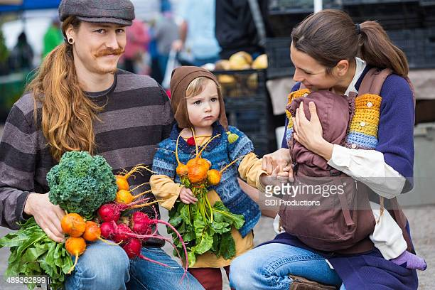 Young hipster familia de compras para producir at outdoor farmer's market