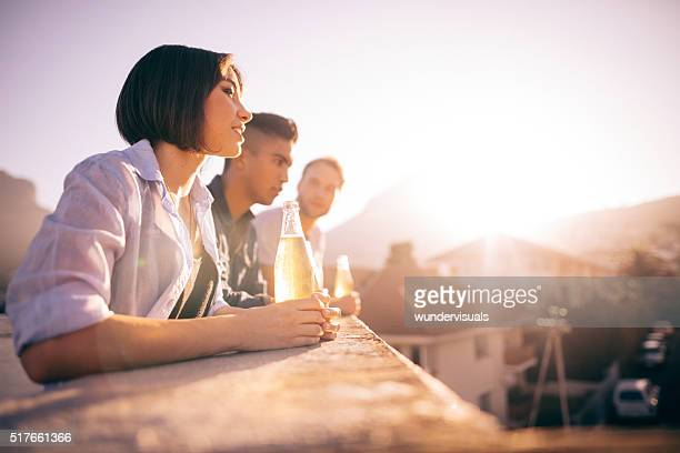 Jeune Hipster amis, boire de la bière et discutant sur le toit