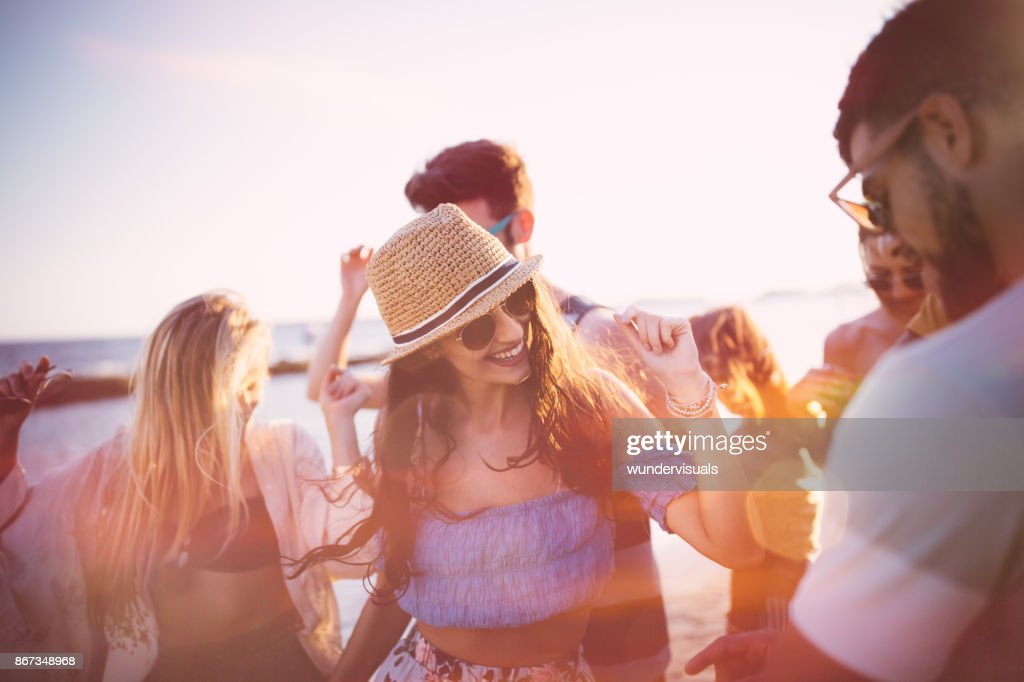 Young hipster friends on summer holidays dancing at beach party : Stock Photo