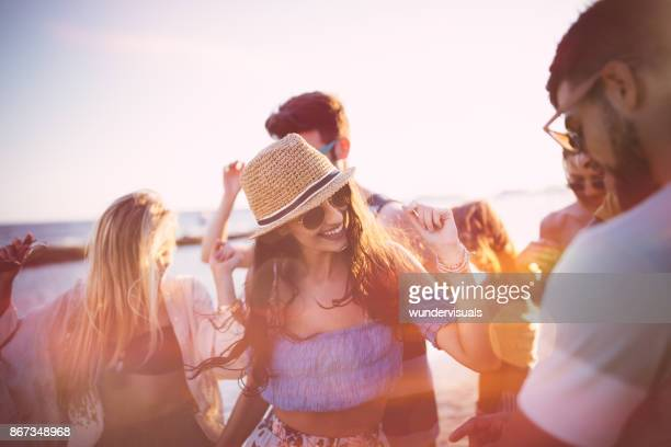 Young hipster friends on summer holidays dancing at beach party