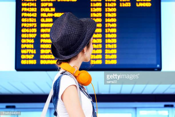 joven hipster chica viajero en el aeropuerto internacional mirando el tablero de información de vuelo, comprobando su vuelo. - cambio horario fotografías e imágenes de stock