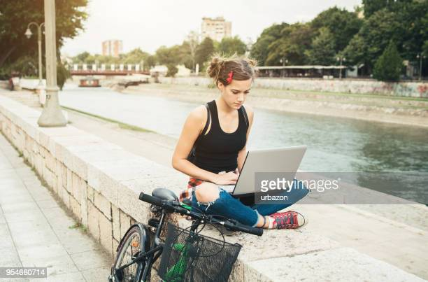 young hipster girl with laptop outside. - nomadic people stock pictures, royalty-free photos & images