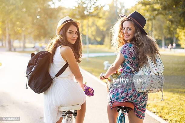 Jóvenes hipster Chicas de pie con una bicicleta en un parque