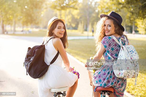 Young hipster girls standing with a bike in  park