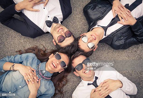 Young hipster group lying down with heads together