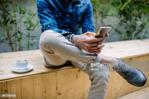 Young hipster guy texting with his mobile phone at the bar and having a cappuccino, close up