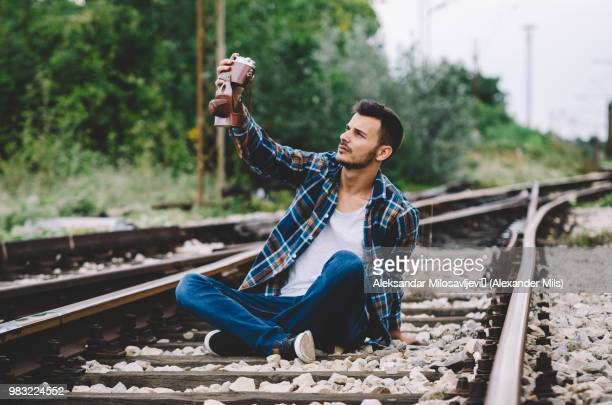 Young hipster guy tourist with camera and bag taking a selfie on the railroad