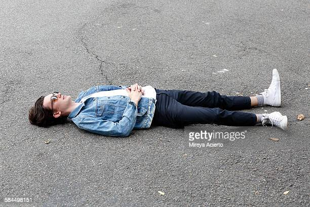 Young hipster male sitting on cement ground