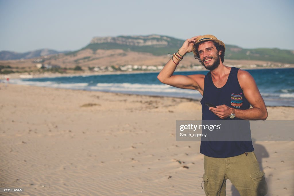 Young Hipster man at the beach using phone : Stock Photo