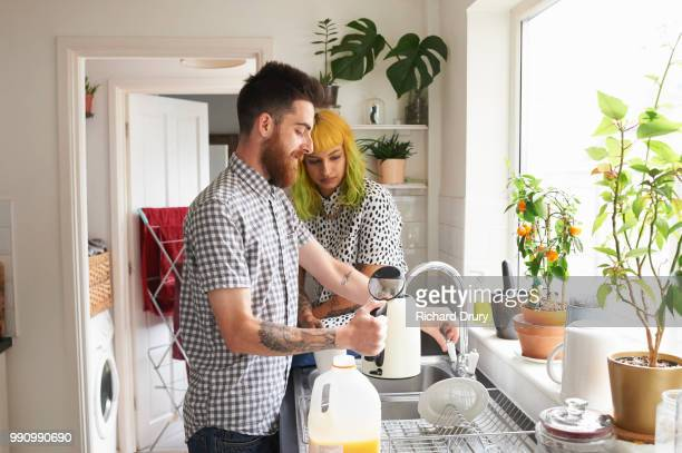 Young hipster man filling a kettle in his kitchen