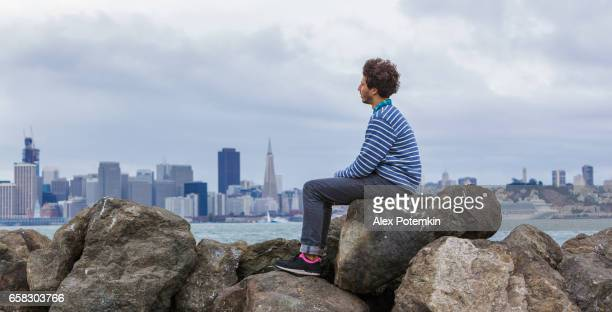 young hipster man in front of san francisco view. - treasure island san francisco stock pictures, royalty-free photos & images