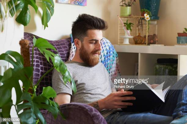Young hipster man reading a book in his living room
