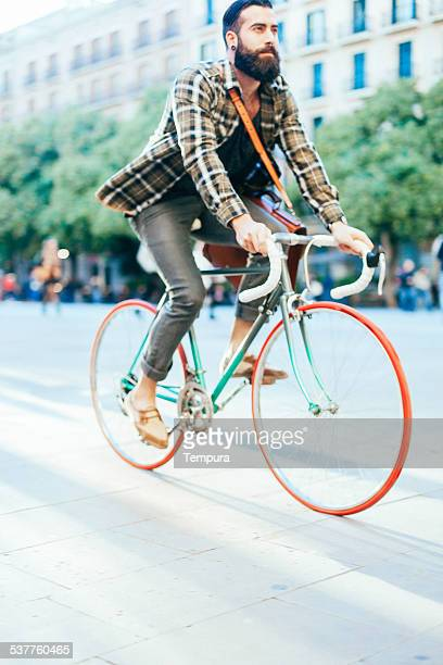 Young hipster man speed with his bike.
