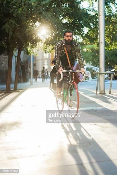 Young hipster hombre velocidad con su bicicleta.