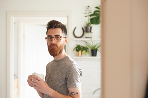 Young hipster man standing in his kitchen holding a mug of tea - gettyimageskorea