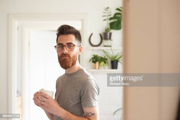 young hipster man standing in his kitchen holding a mug of tea - barba peluria del viso foto e immagini stock